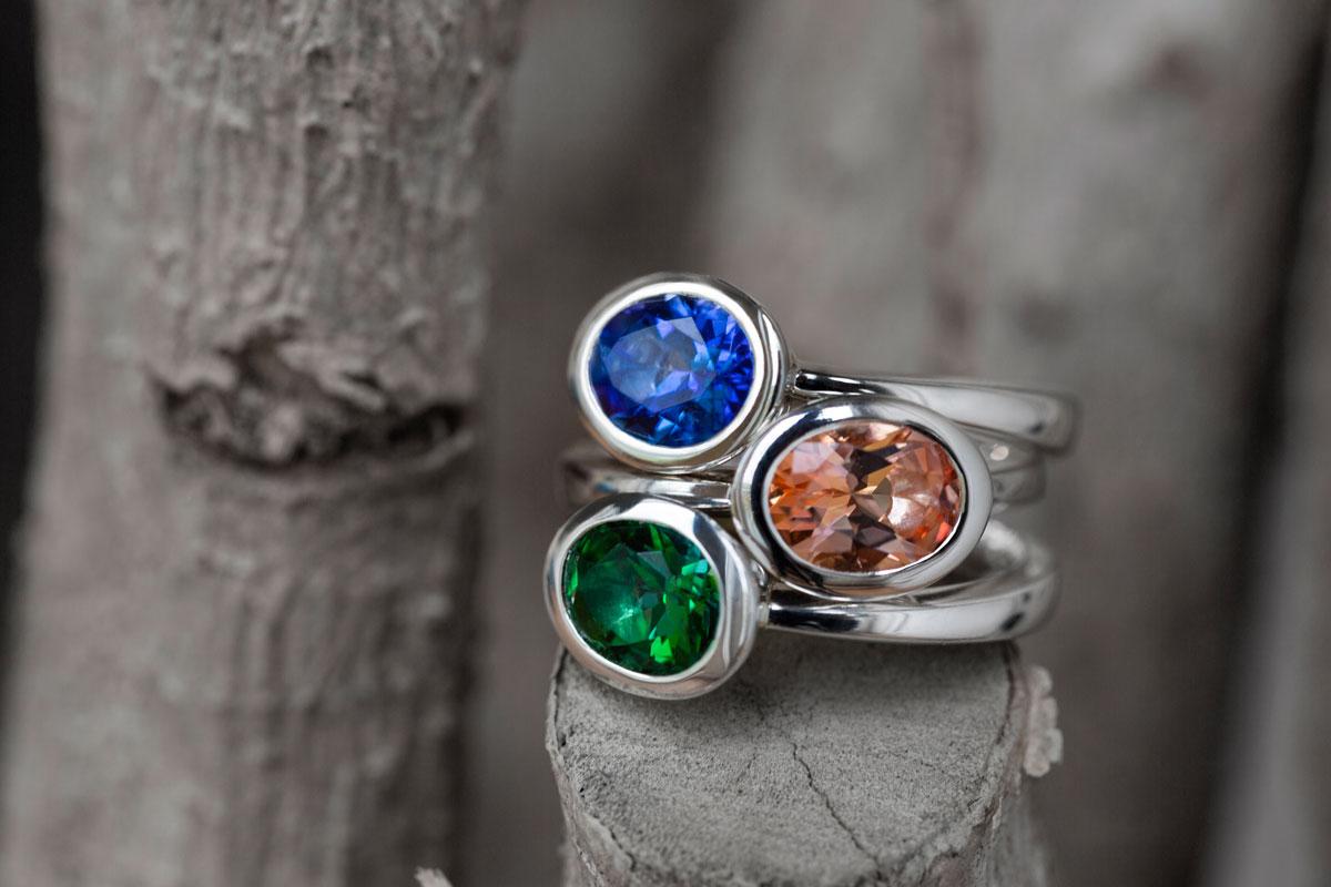 3 übereinander liegende Ringe mit Topasen in Royal Blue, Peach und Rainforest von Fritsch Sterling, fotografiert auf Ästen
