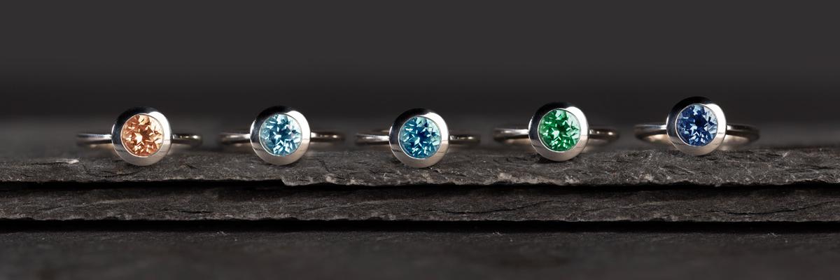 Ringe von Fritsch Sterling, mit rundem 7mm-Topas liegen nebeneinander auf Schiefer. Die Farben sind Peach, Ice Blue, Paraiba, Rainforest und Royal Blue.