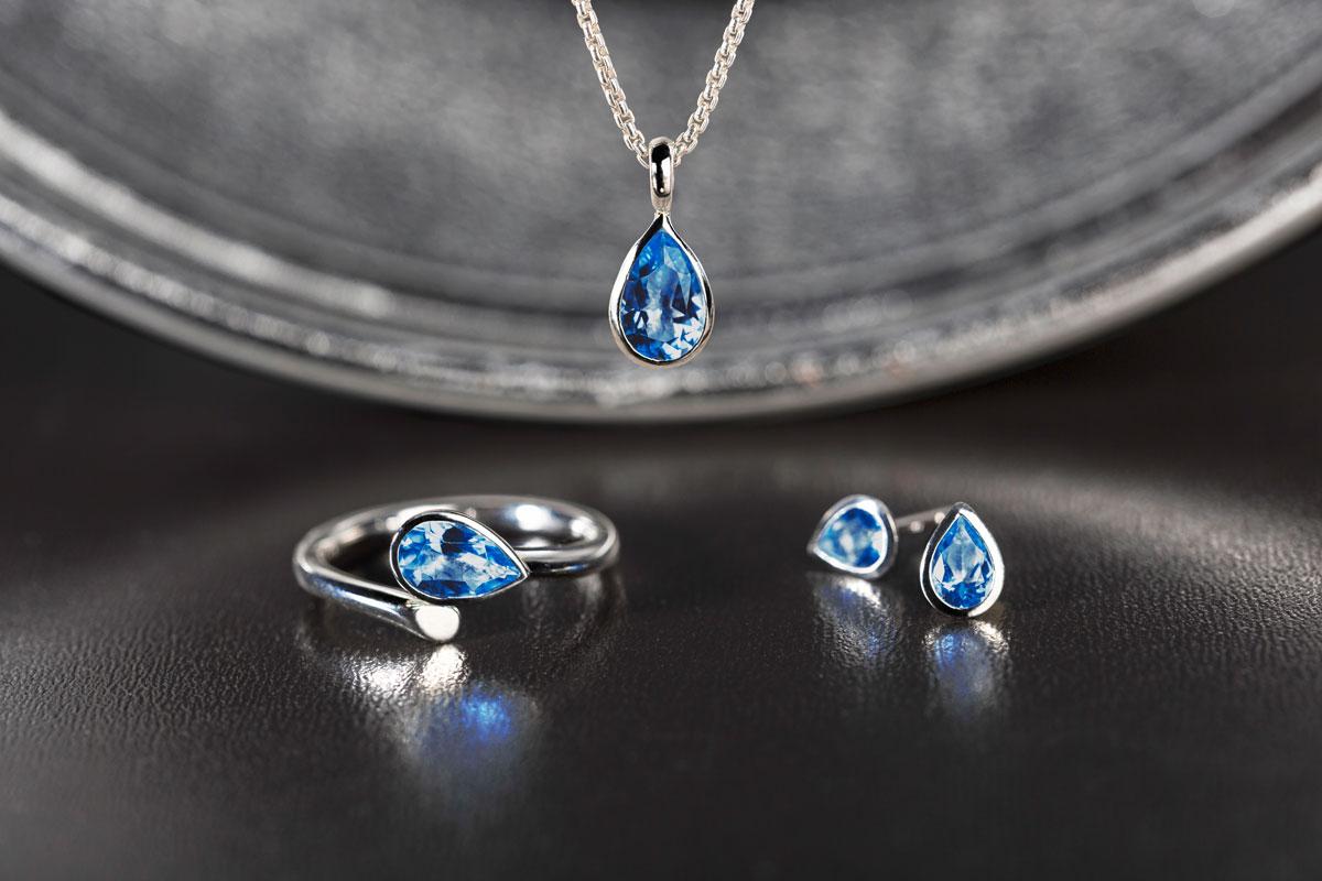 Silberschmuck-Set in Royal Blue von Fritsch Sterling: Ring, KettenAnhänger und Orstecker auf dunkelgrauem Hintergrund