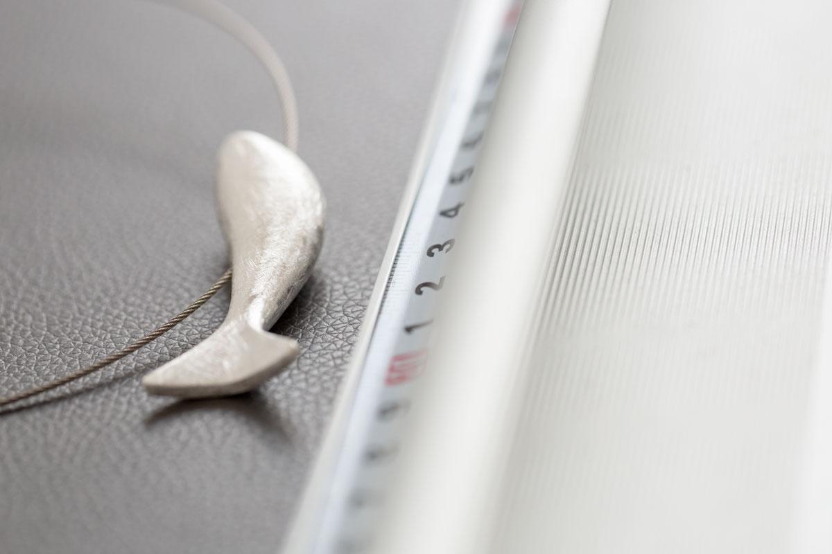 Schmuckanhänger in Form eines Fisches von Fritsch Sterling liegt neben einem Lineal und ist etwa 6 cm groß