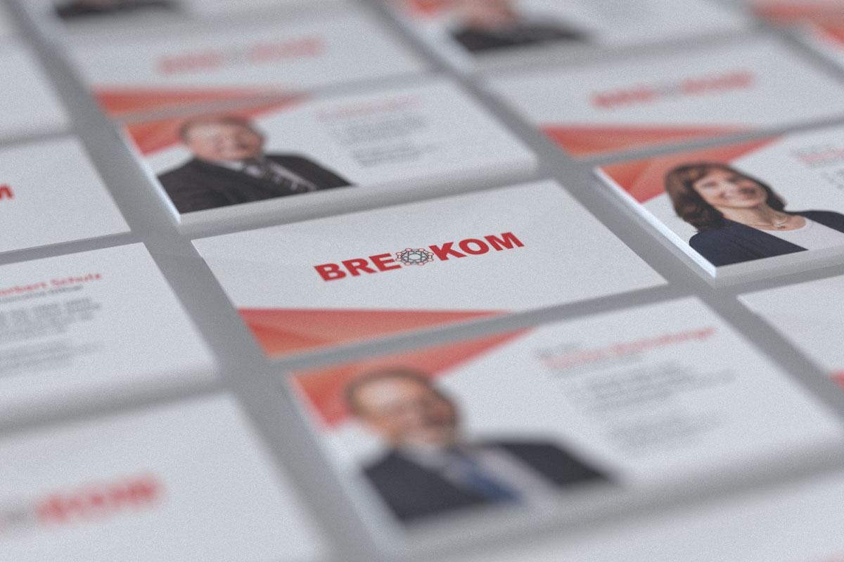 Visitenkarten verschiedener BREKOM-Mitarbeiter liegen nebeneinander; in der Mitte ist die Rückseite mit dem BREKOM-Logo zu sehen