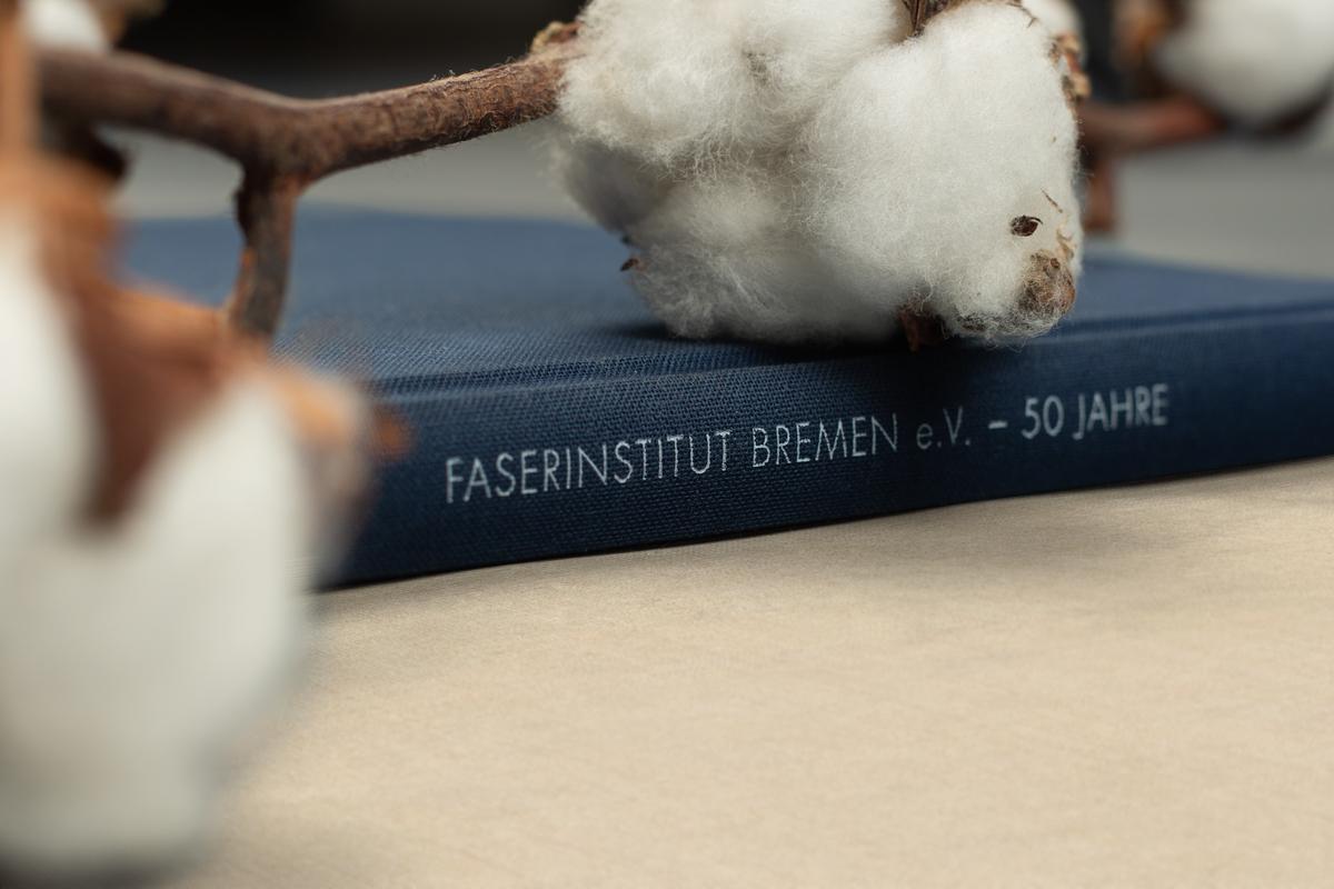 Buchrücken der Festschrift zum 50-jährigen Jubiläum des Faserinstituts Bremen mit Baumwollzweigen