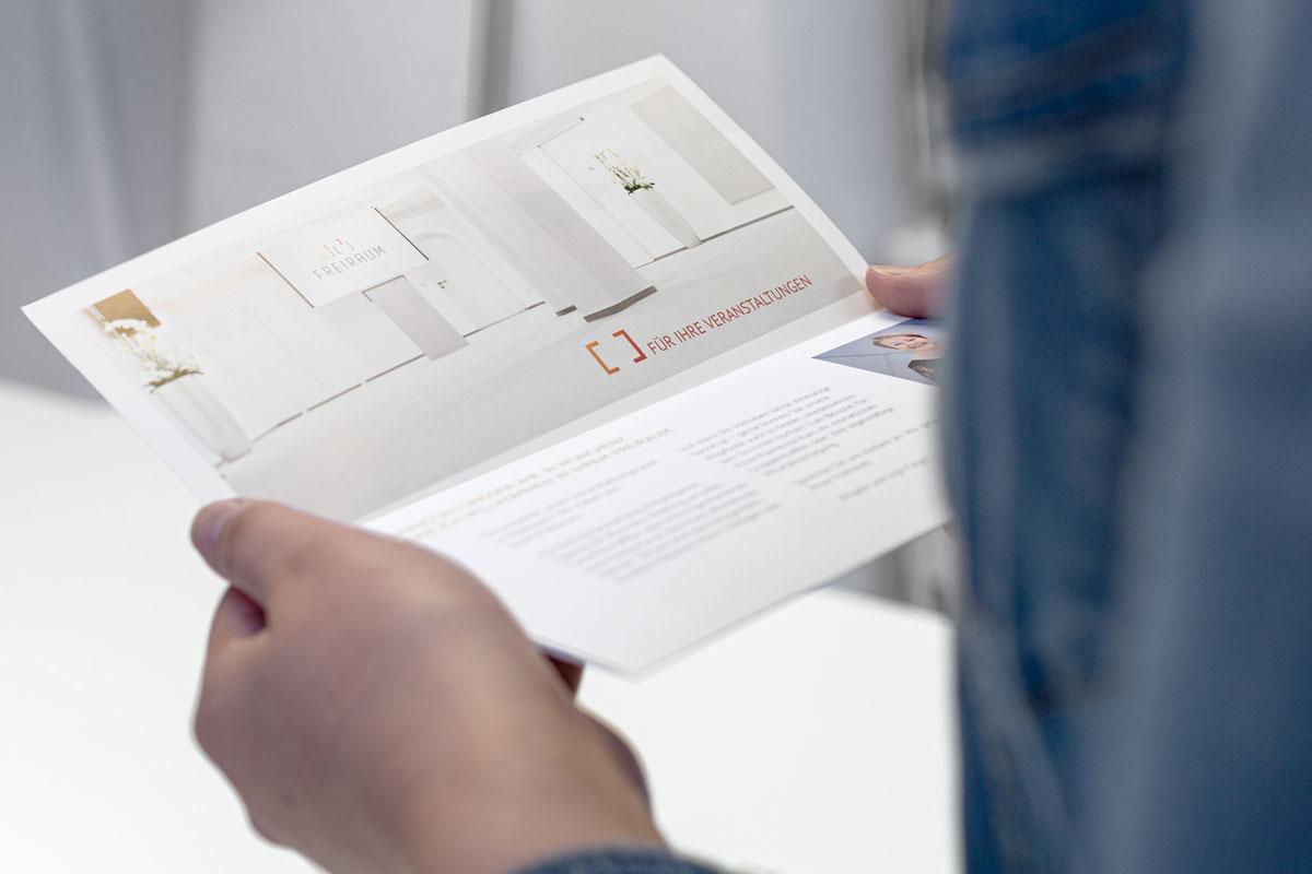 Person hält einteilig aufgeklappten Wickelfalz-Folder von Freiraum in der Hand