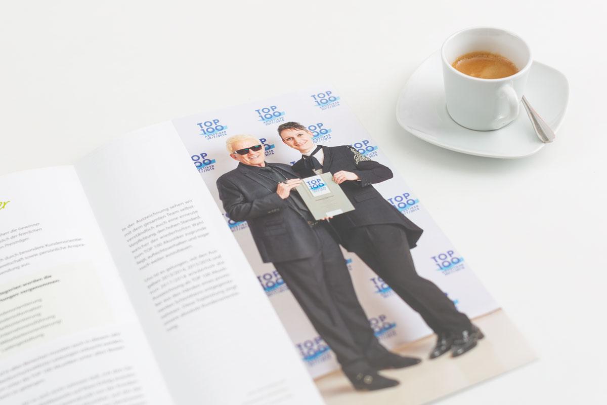 """Kundenmagazin """"Meine Hörwelten"""" von Hilkenbach Hörwelten liegt aufgeklappt da und zeigt Janine Otto und Heino. Daneben steht eine mit Expresso gefüllt Tasse"""