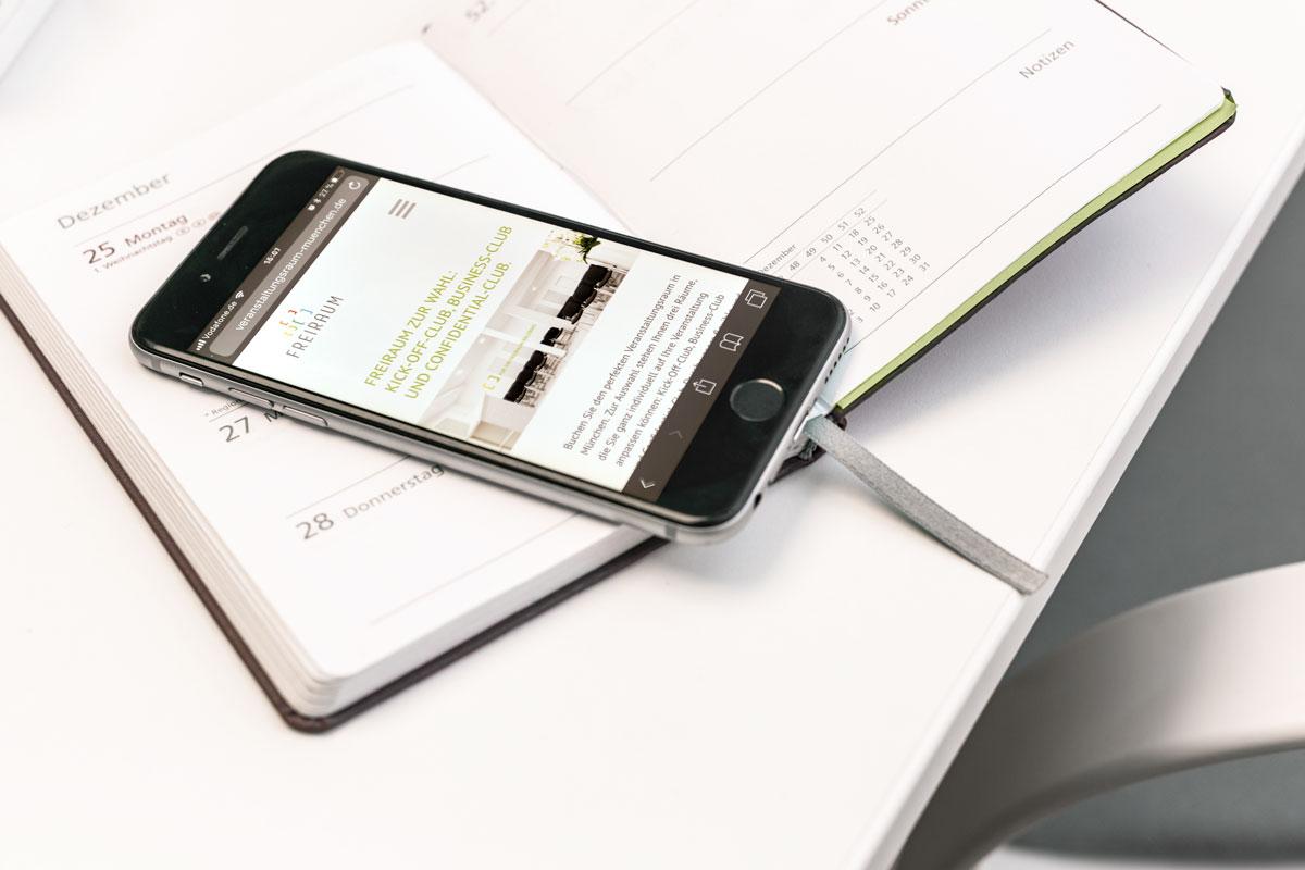 Die Freiraum-Website, dargestellt auf einem Smartphone, das auf einem Kalender liegt
