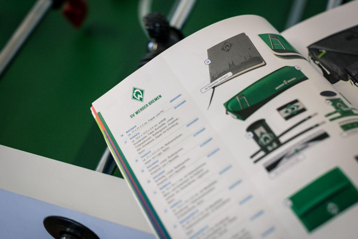 Aufgeklappter Trade-Con-Produktkatalog zeigt Werder-Fanartikel