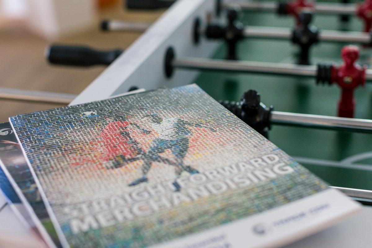 """Katalog von Trade Con """"Straight forward merchandising"""" liegt auf einem Kickertisch"""