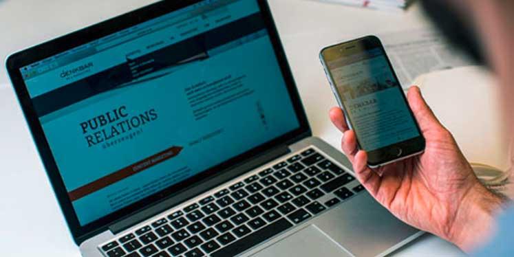 Mann surft mit Macbook Smartphone auf der Denkbar-Website