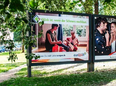 """Plakat der Eurapon-Kampagne """"Glück ist, wenn der Schmerz nachlässt."""" Es zeigt ein Kind, dass seine Mama verarztet, die auf einen Legostein getreten ist."""