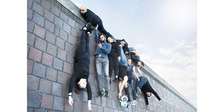 Werbeagentur Teambild von a&o zeigt eine optische Illusion, die den Eindruck erweckt, dass die Mitarbeiter von einer Mauer hängen