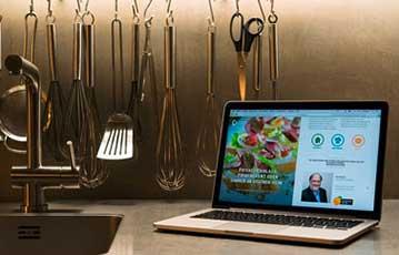 Bild zeigt eine Küchenzeile auf der ein Laptop steht, auf dem gerade die SJS-Catering-Website geöffnet ist