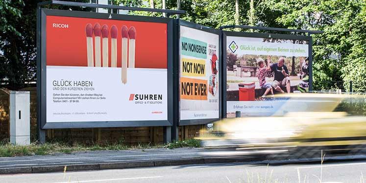 """Plakat von Suhren an einer Straße mit der Headline """"Glück haben und den kürzeren ziehen""""; die Abbildung darauf zeigt Streichhölzer, darunter ein abgebrochenes"""