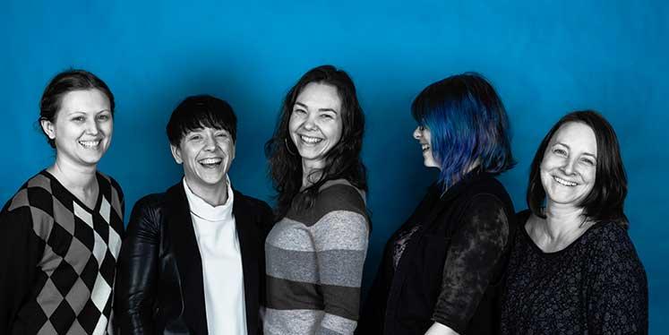 Jasmin, Rebecca, Julia, Nadja und Melanie von Werbeagentur a&o in schwarz-weiß vor cyan Hintergrund